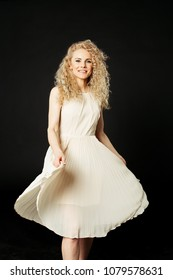Close up studio portrait of a pretty curly blonde woman, wearing light dress, spinning around and looking at the camera, against plain studio background