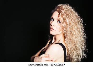 Close up studio portrait of a pretty curly blonde woman, wearing black dress, looking at the camera over the shoulder, against plain studio background