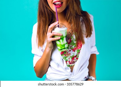 Close up studio portrait of sexy hipster woman with full lips, wearing bright outfit, holding and drinking tasty green smoothie milkshake , sweet pastel colors, ming blue background.