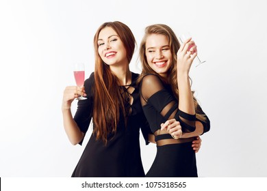 Close up studio portrait of two pretty models, best friends with glass of  champagne posing  on white  background. Red lips, black party dress.