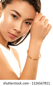 Close up studio portrait of a young Asian lady with nude make-up. The girl with a dainty golden bracelet on her wrist, one hand at her forehead, posing on the white background, looking at the camera.