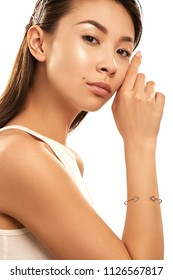 Close up studio portrait of a young Asian lady with nude make-up. The girl with a delicate triangle bracelet on her wrist, posing on the white background, touching her face, looking at the camera.