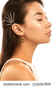 Close up studio portrait of a young Asian lady with nude make-up. The side view of the girl with bobby pins in her hair and delicate earrings, posing on the white background with her eyes closed.