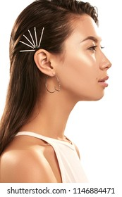 Close up studio portrait of a young Asian lady wearing abstract face-shaped hoop earrings. The side view of the brunette girl with slicked back hair with bobby pins, posing over the white background.