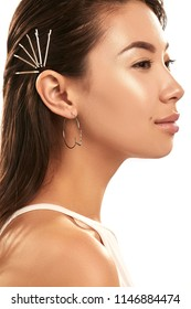 Close up studio portrait of a young Asian lady wearing hoop earrings. The side view of the beautiful brunette girl with slicked back hair with bobby pins, posing over the white background, smiling.