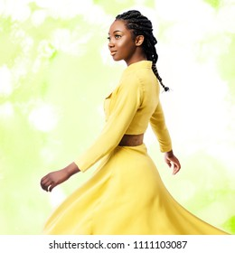Close up studio portrait of young attractive african woman in yellow dress.Girl with braided hairstyle swaying silky dress against colorful green background.