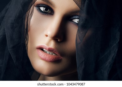 Close up studio portrait of young beautiful sexy woman with smoky eyes makeup, nude lips, posing with black tulle, looking at camera