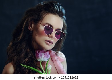 Close up studio portrait of young beautiful sexy model woman wearing trendy violet sunglasses, holding tulip, posing on dark background. Fashion, beauty concept. Copy, empty space for text
