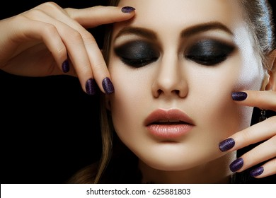 Close up studio portrait of young beautiful woman with healthy flawless skin, big lips, smokey eye make up, dark purple nails posing on black background. Model touching her face. Female beauty concept