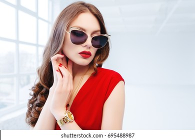 Close up studio portrait of young beautiful luxury woman posing in white room. Model with long hair, red lips, wearing sunglasses, wrist watch. Female fashion concept. Copy, empty space for text