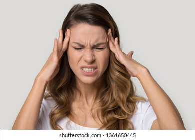 Close up studio portrait young female closed her eyes touching massaging temples suffering from pain headache having high blood pressure, unhealthy stressed millennial frowning woman migraine concept