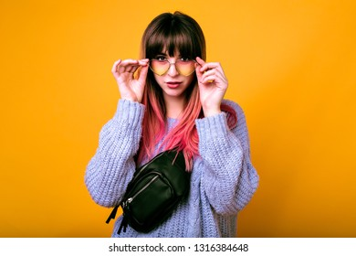 Close up studio portrait of young stylish hipster woman with trendy pink ombre hairs, looking on camera, wearing blue cozy sweater and leather bum bag, hearted sunglasses, spring mood.