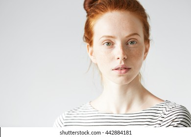 Close up studio shot of beautiful redhead Caucasian young woman with healthy clean skin with freckles, in striped shirt looking at the camera with calm and serious expression. Selective focus