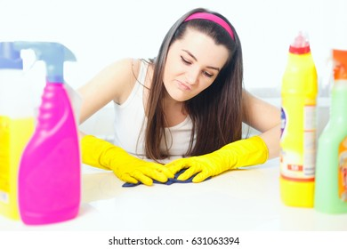 Close up studio shot of housekeeper. Beautiful woman cleaning table with spray. Woman wearing gloves.