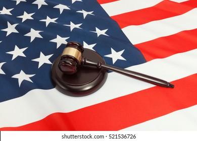 Close up studio shot of a judge gavel and a soundboard over flag of USA