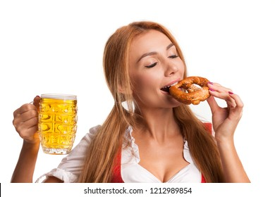 Close up studio shot of a stunning sexy Bavarian woman in dirndl biting a pretzel isolated on white. Gorgeous Oktoberfest waitress celebrating with a mug of beer and snack, copy space