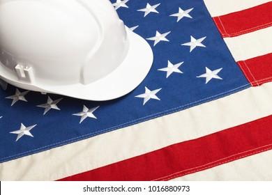 Close up studio shot of a white color construction helmet over USA flag