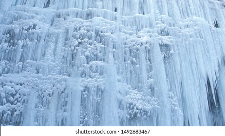 CLOSE UP Stunning frozen waterfall icicles on rocky mountain cliff on winter day. Winter cascade frozen into numerous white icicles. Waterfall falling past hundreds of icicles. Winter wonderland