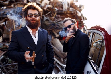 Close up of a stylish brutal bearded mens in black suits and sunglasses smokes cigars near vintage car on the iron dump background and posing at the camera .Gentlemen's club.Horizontal view.
