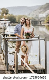 Close up of stylish couple in embrance on quay with nature background. Girl in white dress with pink fresh flowers