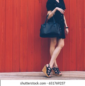 Close up of stylish female leather bag outdoors. Fashionable and high style expensive female bag. Sales bag fashion concept. Part of body. On red wood background. High Wedge Sandals.
