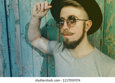 Close up of stylish hipster man in hat and sunglasses wearing fashionable mustaches. Fashion, people, lifestyle concept