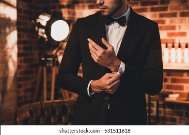 Close up of stylish man in black suit fastening cufflinks in loft