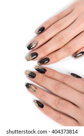 Close up of stylish manicured hands painted black and glittery gold against a white background