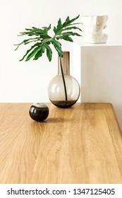 Close up of stylish and minimalistic interior with tropical leaf in vase, woooden table, candles and stand with sculpture head. Modern room with design accessories. Eclectic home decor. Details.