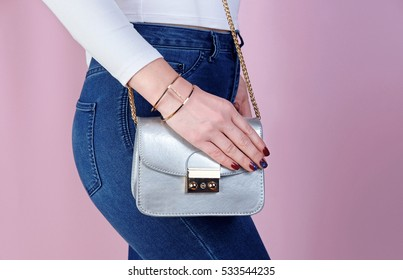 Close up stylish woman in jeans with small silver bag and bracelet. fashion concept.