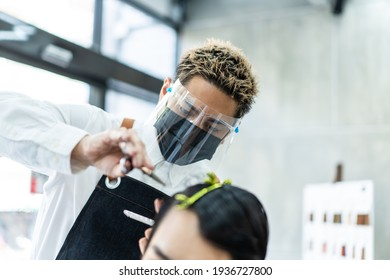Close up of stylist Asian male hairdresser wearing a face shield and mask for protection and practicing social distance during Covid 19 pandemic giving haircut service to male customer in modern salon