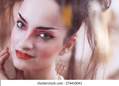Close up stylized portrait of a Japanese geisha with bright make up standing at the window watching the rain