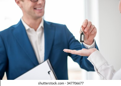 Close up of successful estate agent selling a house. He is standing and giving a key to the woman. The man is smiling