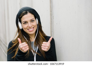 Close up of successful sporty woman doing thumbs up gesture. Fitness workout goals and success concept. Female athlete wearing headphones.