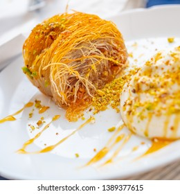 Close up of a succulent Greek dessert. Greek kataifi with honey yogurt and grated pistachios on a white plate and a blurred background. Square view