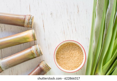 Close up sugar cane on rustic wood table.Brown sugar and cane on wood background.