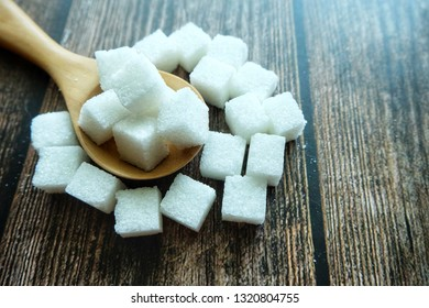 Close up of sugar cube on wooden spoon.