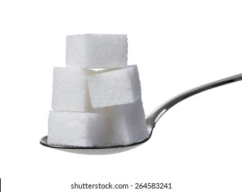 close up of sugar cubes and spoon on white background