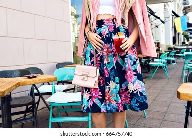 Close up summer fashion details, woman in stylish elegant outfit, holding tasty berry cocktail, floral skirt pink jacket, outdoor city background, cute terrace cafe, midi trendy skirt.