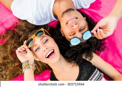Close up summer portrait of  cheerful young couple  having fun and make grimace. Bright sunny colors .  Beautiful stylish girl and her  handsome man lying on mat. Wearing sunglasses .