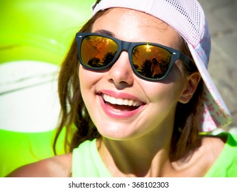 Close up summer portrait of a young girl hipster beautiful brunette teenage girl in sunglasses  having fun at pool party.Happy summer vacation girl. Beautiful caucasian woman having fun and smiling
