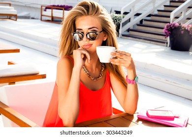 Close up summer sunshine portrait of amazing young lady with morning cup of her cappuccino,bright stylish dress,vintage sunglasses on table,enjoy morning breakfast in hotel.summer colors.accessory