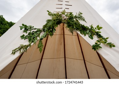 Close up of the summer wedding tipi in a field. Tee pee built on green grass. Traditional teepee tent wigwam located in nature. Natural decoration for wedding.