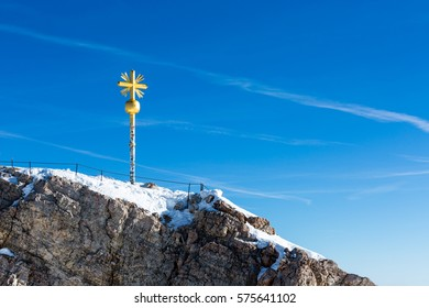 Close up of the summit cross and summit of Germany's highest mountain, the Zugspitze, on a sunny, cloudless winter morning with clear blue sky.