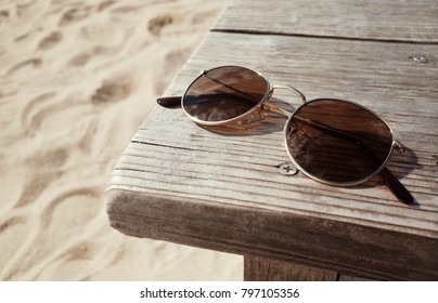Close Up Sunglasses on Wooden Chair on Sand of The Beach