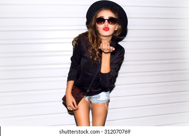 Close up sunny portrait of beautiful woman with fluffy brunette long hairs,smiling,having fun on the white wall,Sending kiss,wearing vintage sunglasses,Black leather outfit and hat,red lipstick smile