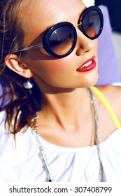 Close up sunny portrait of cute pretty hipster girl enjoy her vacation on tropical island, laying near pool, vintage sunglasses, bright makeup, joy, spa, relax, sunbathe.
