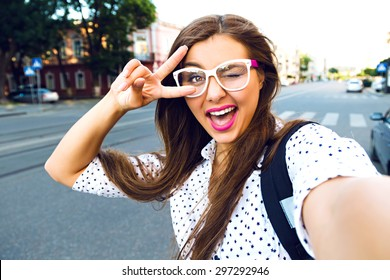 Close up sunny portrait of young happy pretty girl making selfie and smile, wearing cute hipster clear glasses, lovely emotions, long brunette hairs, perfect ski, bright make up.