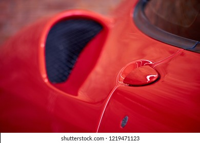 Close up of supercar door handle with side scoop air vent. Concept of car detailing and paint protection background. Detail of sportscar aerodynamic with reflection on red paint after wash & wax.