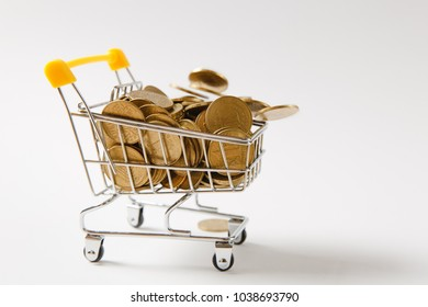 Close up of supermarket grocery push cart for shopping with yellow plastic handle with golden coins falling into it isolated on white background. Concept of shopping. Copy space for advertisement.